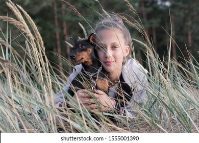 pretty blonde teenage girl lying in grass with her dog black mini pinscher at summer beach