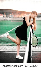 A pretty blonde is tired of a grueling tennis game. Portrait of a beautiful female athletes with a tennis racket.