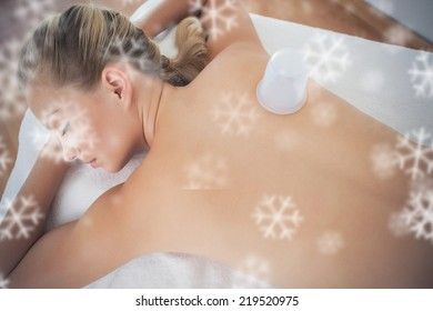 Pretty blonde with vacuum cup on her back against snowflakes