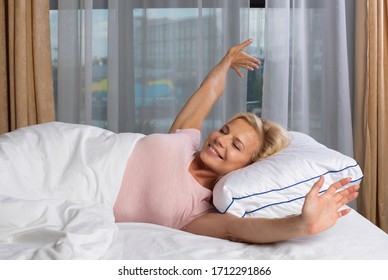 Pretty blonde woman in bedroom by morning