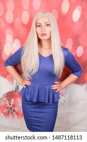 pretty blonde woman in blue peplum dress on red xmas background