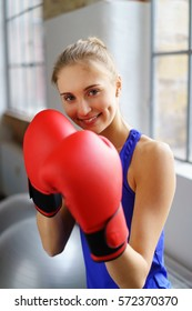 Pretty blonde woman in blue top and red boxing gloves keeping hands to her face while looking at camera and smiling with window background