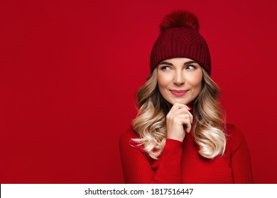 Pretty blonde woman with curly hair touching her chin, wears red wool turtleneck and hat, isolated on red studio wall, enjoys the winter weather, thinking and looking at blank space for advertising