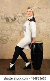 Pretty blonde woman in dress poses near black druml in studio