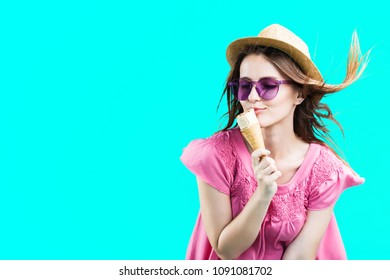 Pretty blonde woman dressed in rose shirt, hat and sunglasses eating wafle icecream before blue background