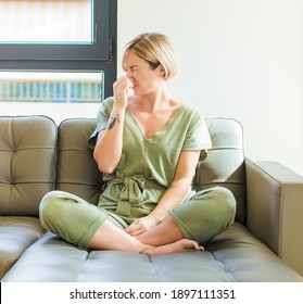 pretty blonde woman feeling disgusted, holding nose to avoid smelling a foul and unpleasant stench