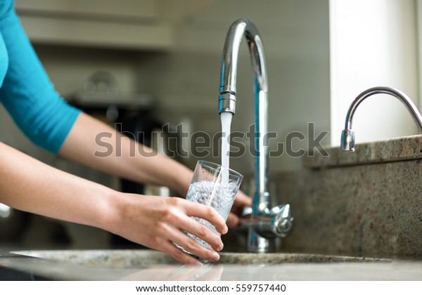 Pretty blonde woman filling a glass of water at home