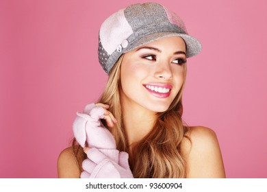 A pretty blonde woman giving a beautiful big smile wearing corduroy cap