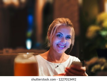 Pretty blonde woman look at smartphone
