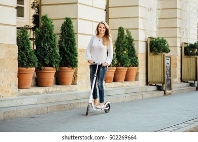 Pretty blonde woman riding a kick scooter in a European city