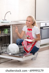 Pretty blonde woman showing thumb above clean dishes in dishwasher