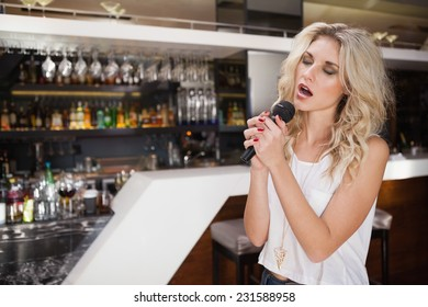 Pretty blonde woman singing while closing her eyes at the nightclub