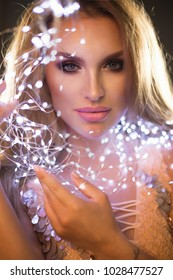 Pretty blonde woman smiling  with magic sparkle in her hands. Led Lights