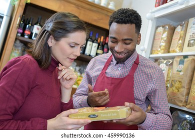 pretty blonde woman speaking with seller at supermarket