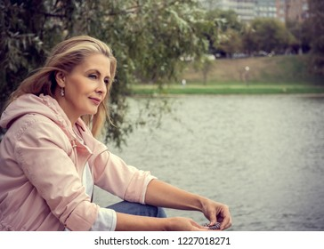Pretty blonde woman walk in the park and look at smartphone