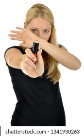 Pretty blonde young woman is protecting herself with pepper spray or irritating gas for self defense isolated on white
