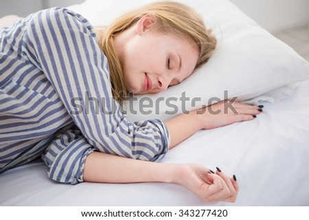 Pretty blonde young woman sleeping in her white bed on the pillow in striped pajamas