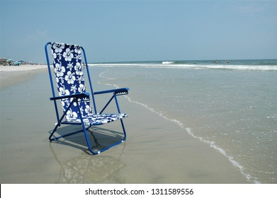 Pretty blue beach chair in the sand at the seashore.