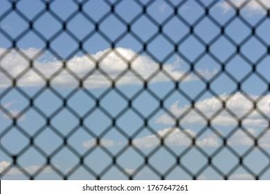 A pretty blue sky as seen through a wire fence