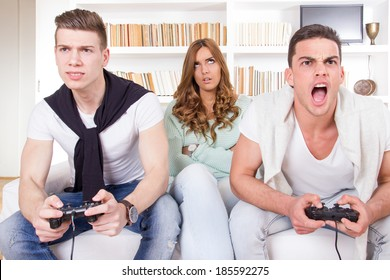 pretty bored women between two casual passionate men playing video game with joystick