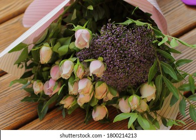 Pretty bouquet with pink roses and other small flowers, color tender roses and purple flowers