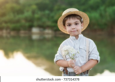 Pretty boy in the straw hat as Tom Sawyer with a bouquet of flowers in front of the lake. The boy smiles.