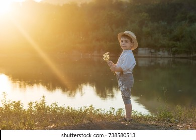 Pretty boy in the straw hat as Tom Sawyer with a bouquet of flowers in front of the lake. The boy smiles. At sunset in sunlight rays in back lighting.