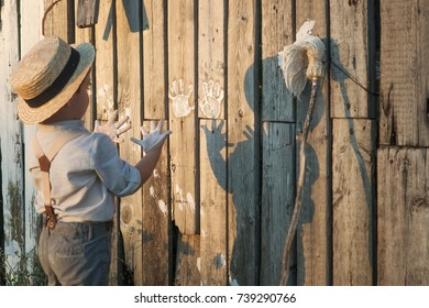 Pretty boy in the straw hat as Tom Sawyer in front of fence with the shadow. The boy paint a wooden fence white paint. The boy paint his palms in white.