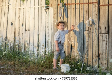 Pretty boy in the straw hat as Tom Sawyer in front of fence with the shadow. The boy paint a wooden fence white paint.