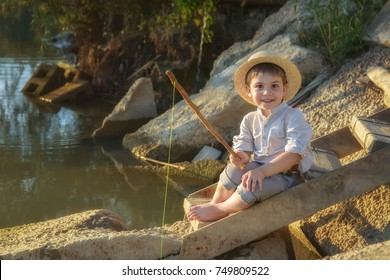 Pretty boy in the straw hat as Tom Sawyer fishing near the lake on the sunset.