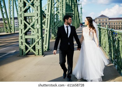 Pretty bride with curly hair and bridegroom standing close to each other on bridge, wedding photo, beautiful couple.