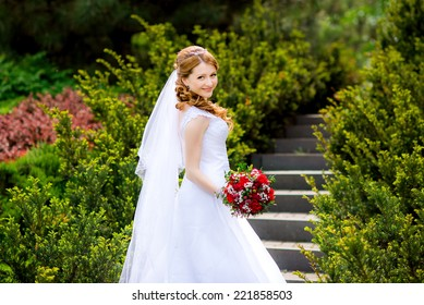 Pretty bride in a park on the stairs with a red wedding bouquet in hands