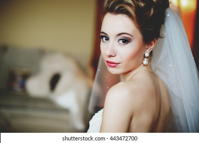 Pretty bride with red lips looks over her shoulder