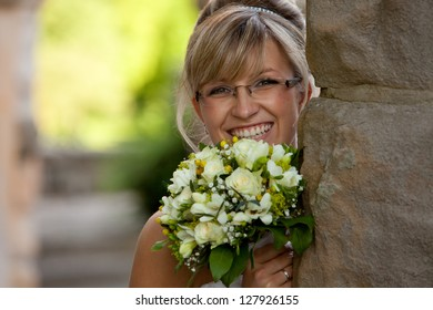 pretty bride wears nice glasses and a bouquet