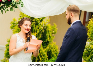 a pretty bride in a wedding dress holds the microphone in her hand and reads the vow to the groom