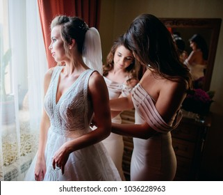 Pretty bridesmaids help beautiful bride to put on a wedding dress before a window