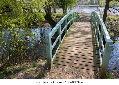 Pretty bridge over stream. Picturesque spring country landscape. Painted wooden footbridge. Quaint rural scene of beautiful English river in Norfolk UK.