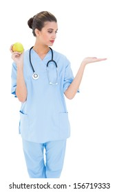 Pretty brown haired nurse in blue scrubs holding a green apple on white background