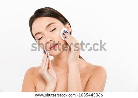 Pretty brunette asian half-naked lady with closed eyes using cotton sponges to remove make up isolated