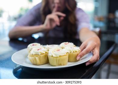 Pretty brunette binging in secret in a coffee shop