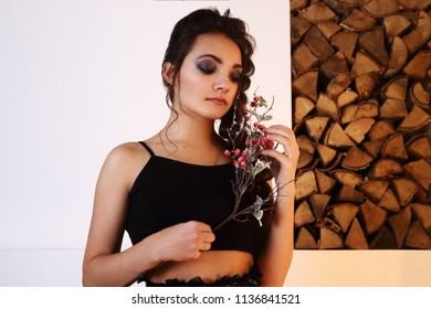 Pretty brunette in black with berries poses in studio with logs