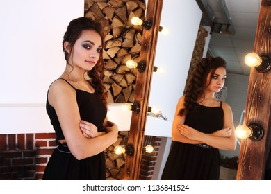 Pretty brunette in black with berries poses in studio with logs and mirror