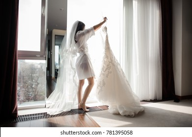 Pretty brunette bride in silk dressing gown and lacy veil holding wedding dress on a hanger near the window