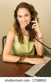 A pretty brunette business professional wearing a green outfit using a notebook computer while on the phone.
