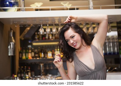Pretty brunette dancing and smiling at the nightclub