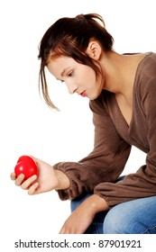 Pretty brunette in depression holding small heart in her hand.