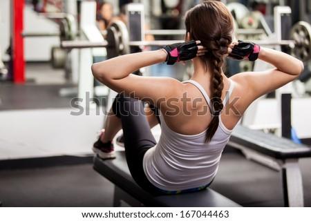 Pretty brunette doing crunches in front of a mirror in a gym