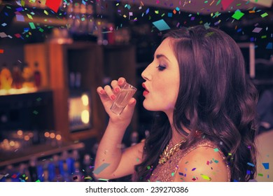 Pretty brunette drinking a shot against flying colours