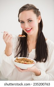 Pretty brunette eating bowl of cereal at home in the kitchen
