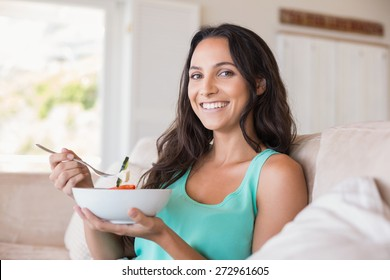 Pretty brunette eating salad on couch at home in the living room